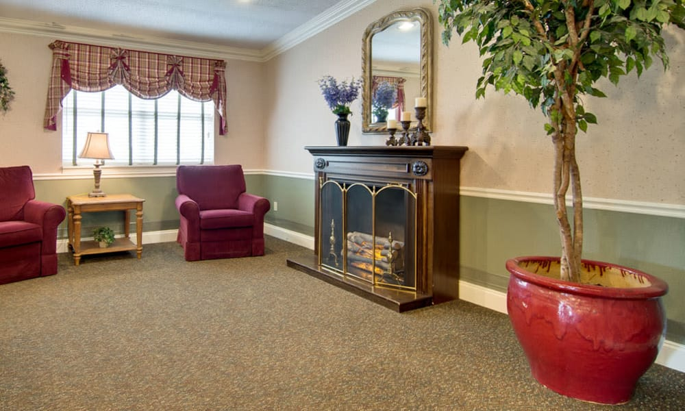 Resident lounge with fireside seating at Heritage Nursing Center in Kennett, Missouri