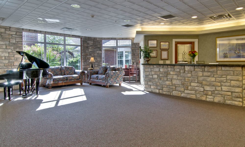 The main lobby with a piano and seating at The Neighborhoods at Quail Creek in Springfield, Missouri