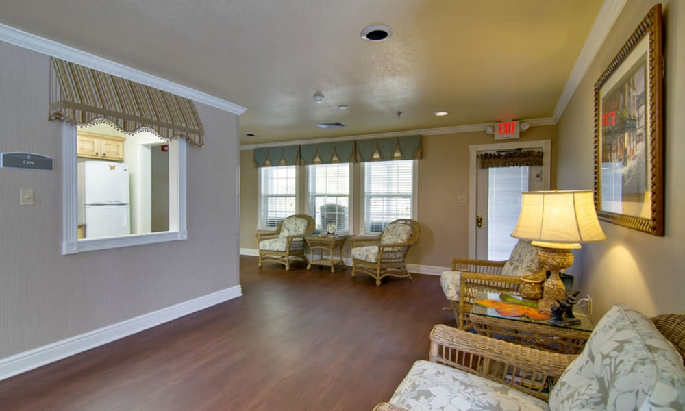 Community lounge with comfortable seating and a view of the kitchen at Asbury Cove in Ripley, Tennessee
