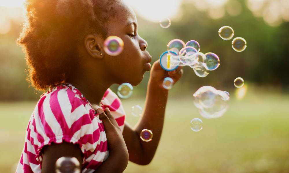 Little girl blowing bubbles at 1330 7th Street in Washington, District of Columbia