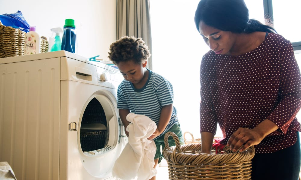 Mother and son starting laundry at Monsenor Romero Apartments in Washington, District of Columbia