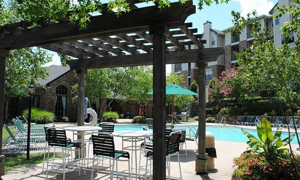 An outdoor lounge area by the pool at Arbors of Pleasant Valley in Little Rock, Arkansas