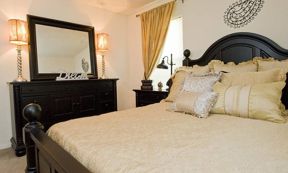 An apartment bedroom with dresser and mirror at Hunter's Ridge in Oklahoma City, OK