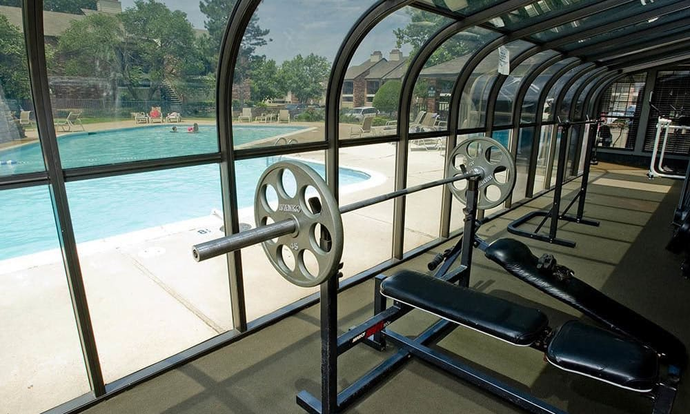 A community gym with a view of the pool at The Warrington Apartments in Oklahoma City, OK
