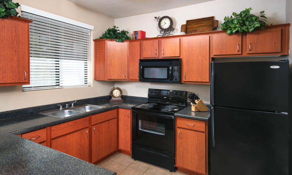 A kitchen with black appliances and granite countertops at Broadstone Desert Sky