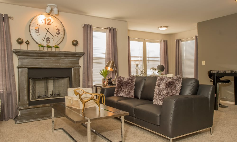 Spacious living room with a fireplace at Cottages at Tallgrass Point Apartments in Owasso, Oklahoma
