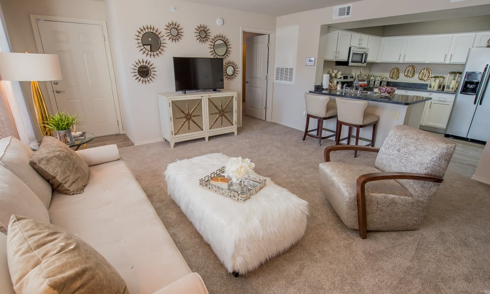 Well decorated living room with plush carpeting at Cottages at Tallgrass Point Apartments in Owasso, Oklahoma