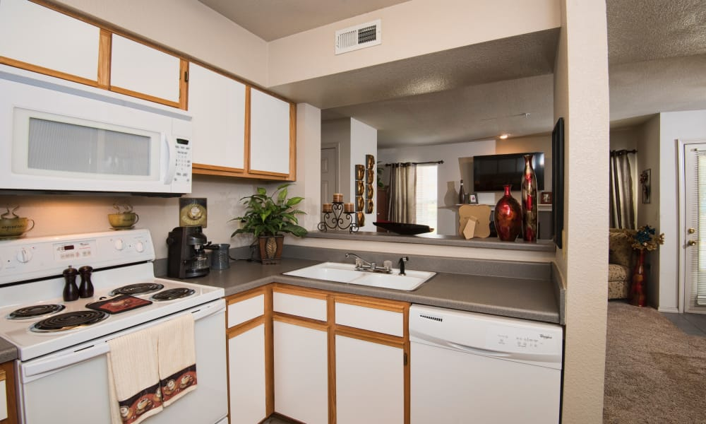 Kitchen with a view of the living room at Crown Chase Apartments in Wichita, Kansas