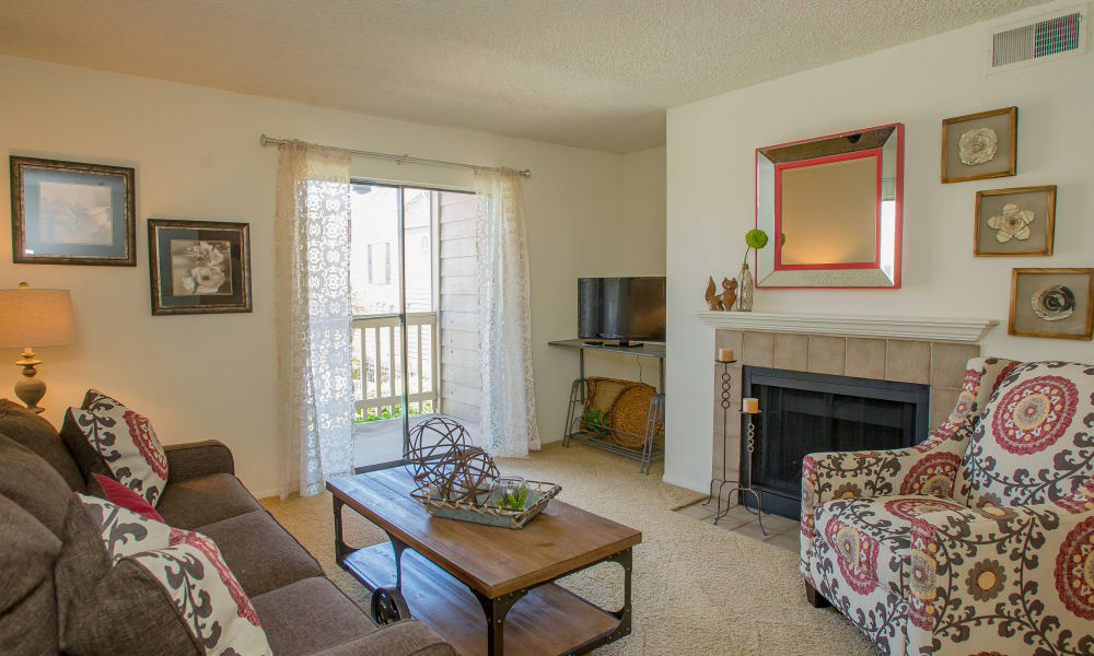 Carpeted living room with a fireplace at Cedar Glade Apartments in Tulsa, Oklahoma