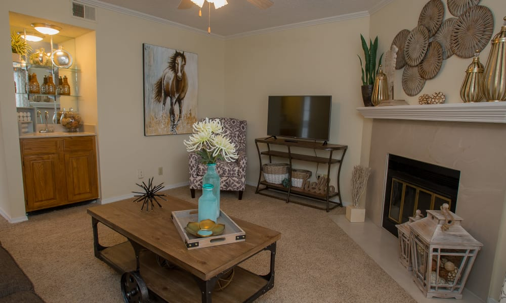 Carpeted living room with a fireplace at Creekwood Apartments in Tulsa, Oklahoma