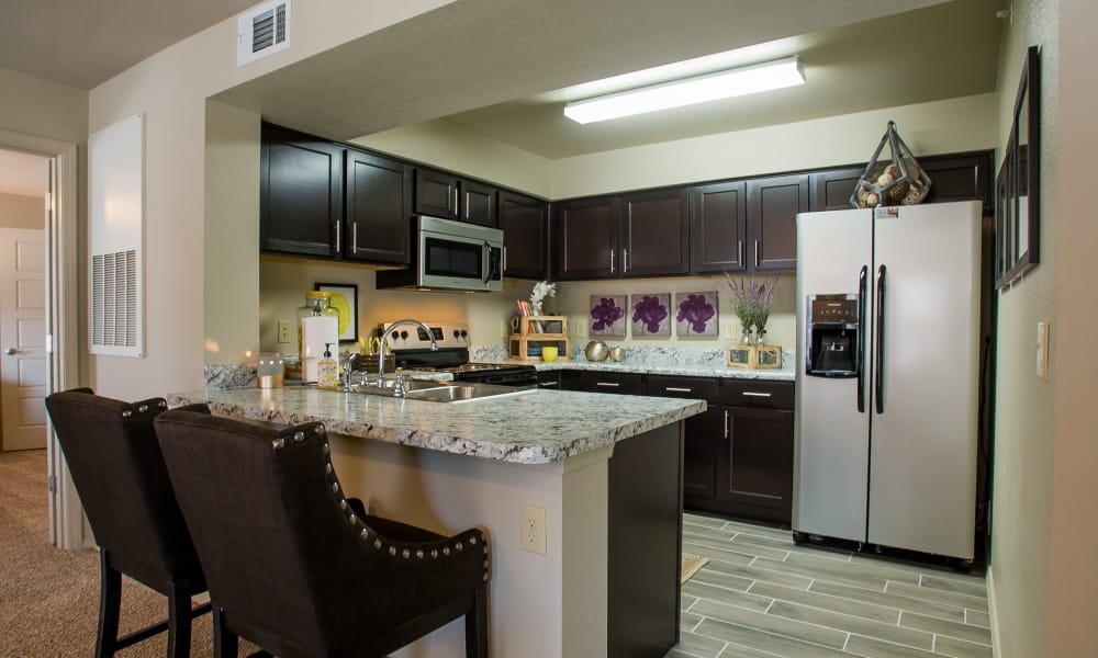 Kitchen with bar seating at Icon at Broken Arrow in Broken Arrow, Oklahoma