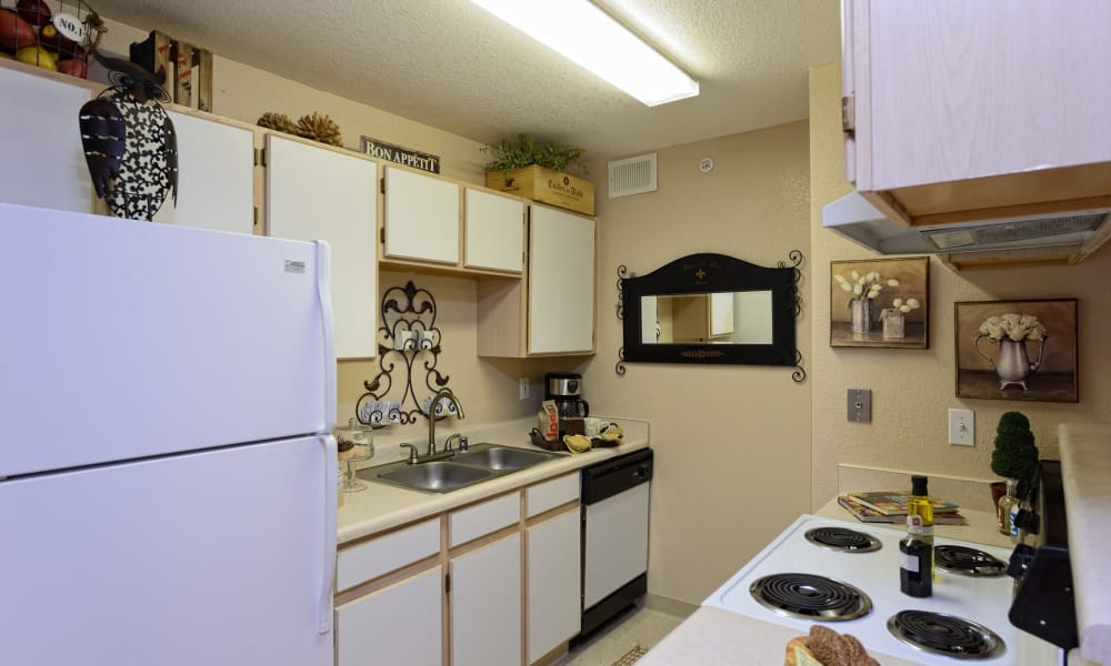 Kitchen with white appliances at Acacia Park Apartments in El Paso, Texas