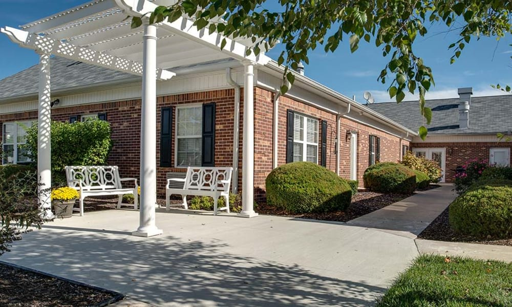 Concrete walkway with outdoor seating at Chestnut Glen Senior Living in Saint Peters, Missouri