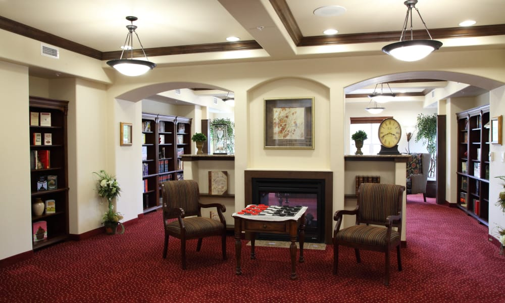 Fireside seating in the library at Cottonwood Estates Gracious Retirement Living in Alpharetta, Georgia