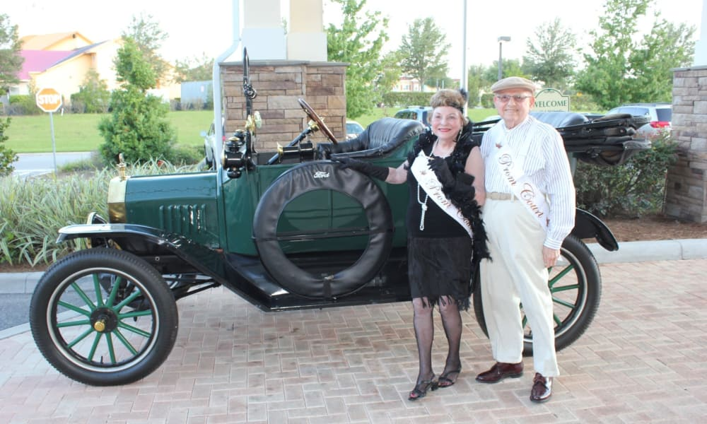 Two residents posing in front of a classic car, dressed for prom at Desert Springs Gracious Retirement Living in Oro Valley, Arizona