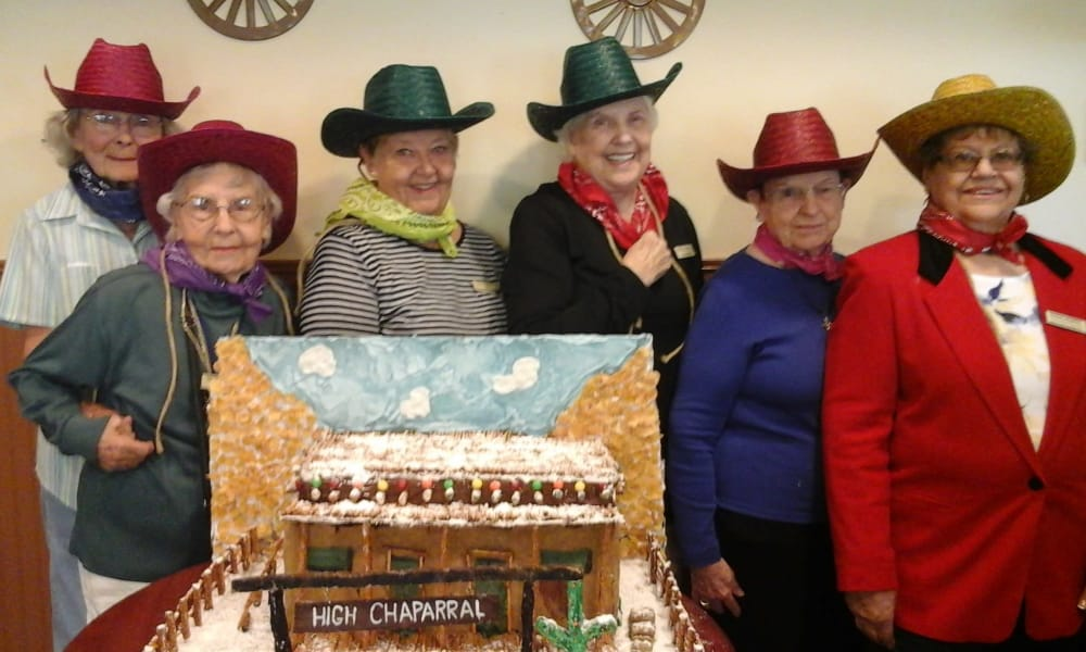 Residents in western clothes posing next to a western gingerbread house at Desert Springs Gracious Retirement Living in Oro Valley, Arizona