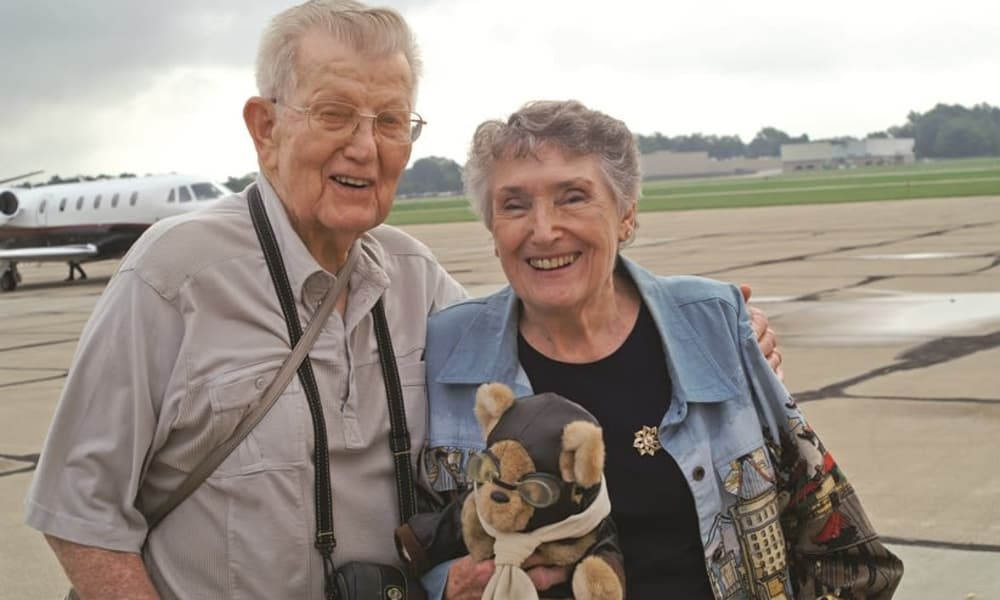 Two residents from Desert Springs Gracious Retirement Living in Oro Valley, Arizona with a pilot teddy bear in front of a plane