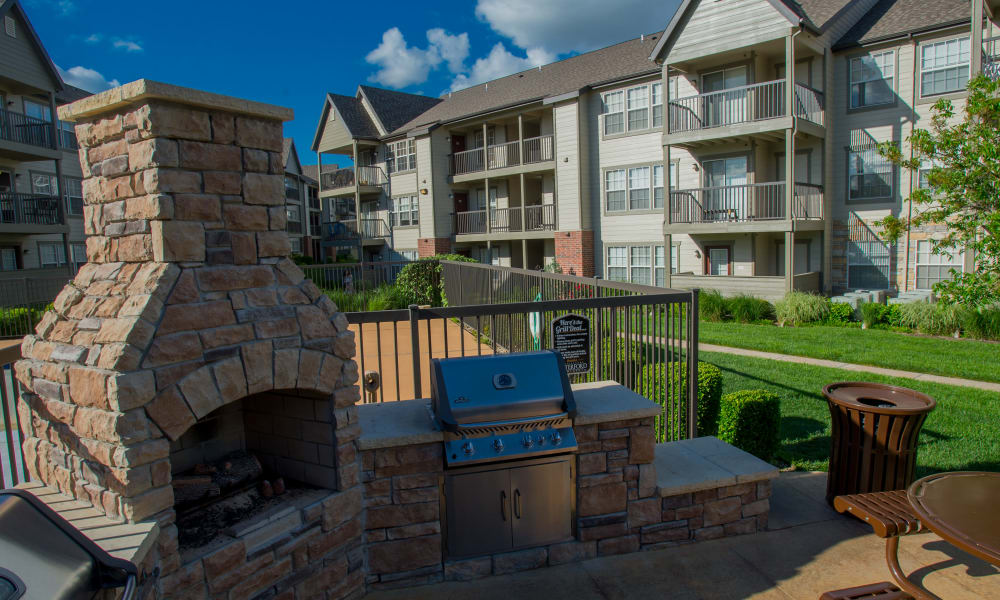 Outdoor patio with a fireplace at Villas of Waterford Apartments in Wichita, Kansas