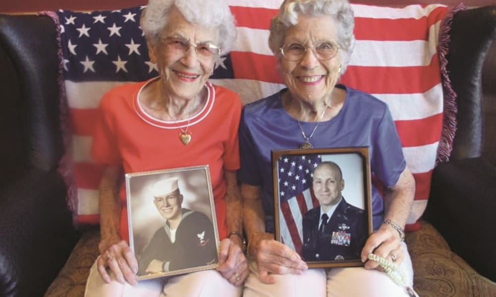 Two residents holding photos of veterans at Estrella Estates Gracious Retirement Living in Goodyear, Arizona
