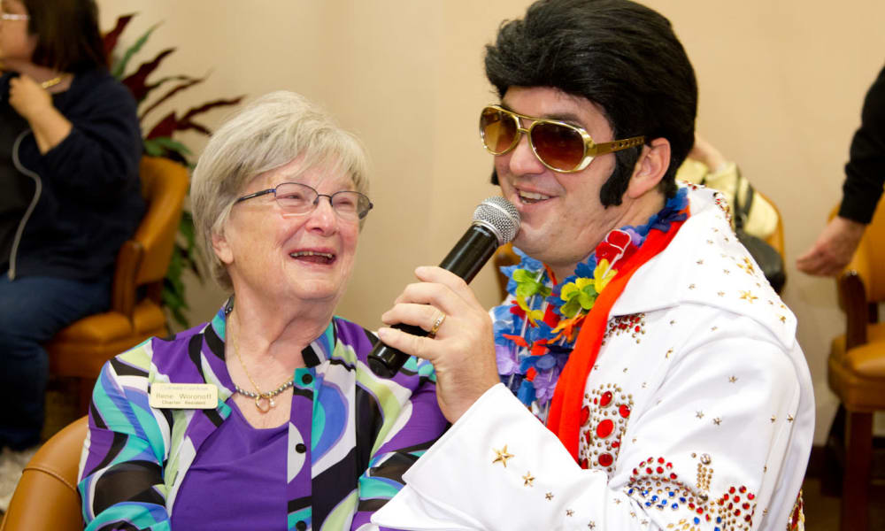 A happy resident listening to an Elvis impersonator sing at Fairview Estates Gracious Retirement Living in Hopkinton, Massachusetts