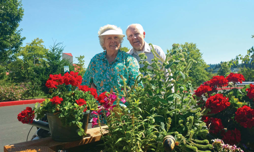 Two residents posing in front of planter box at Glenmoore Gracious Retirement Living in Happy Valley, Oregon
