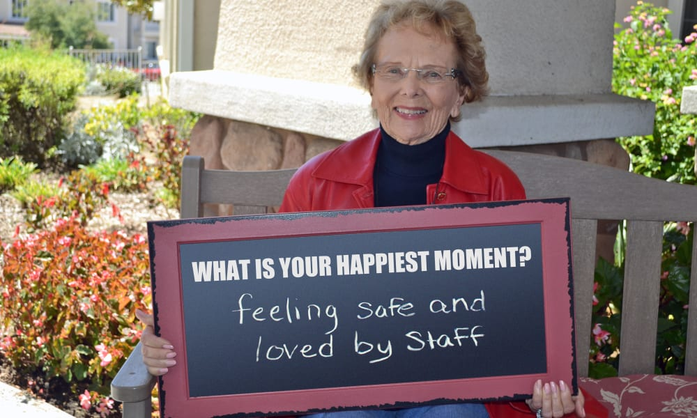 A resident holding a sign with her favorite memory on it at Heatherwood Gracious Retirement Living in Tewksbury, Massachusetts