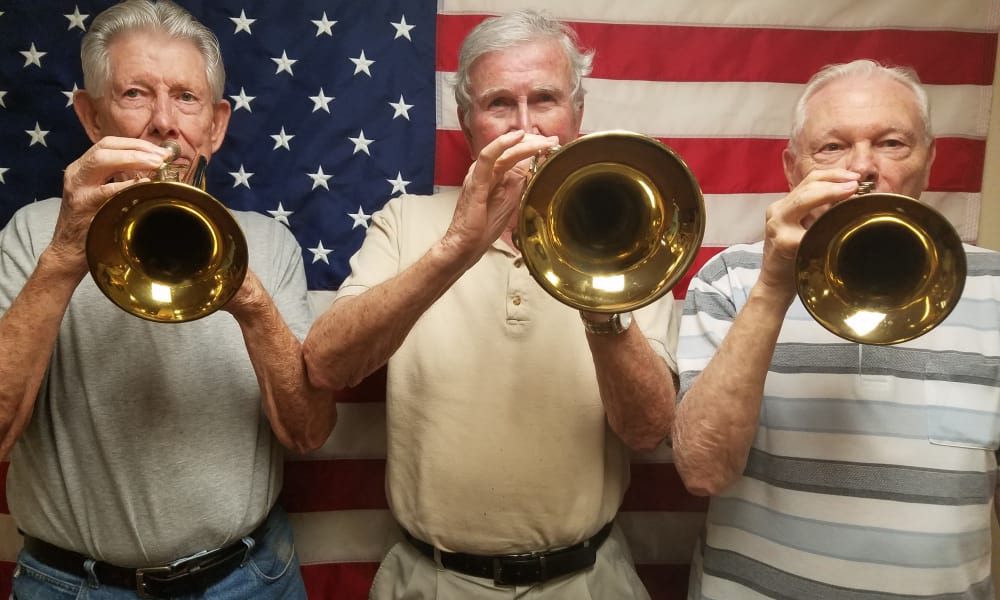 Three residents with trumpets in front of an American flag at Heatherwood Gracious Retirement Living in Tewksbury, Massachusetts