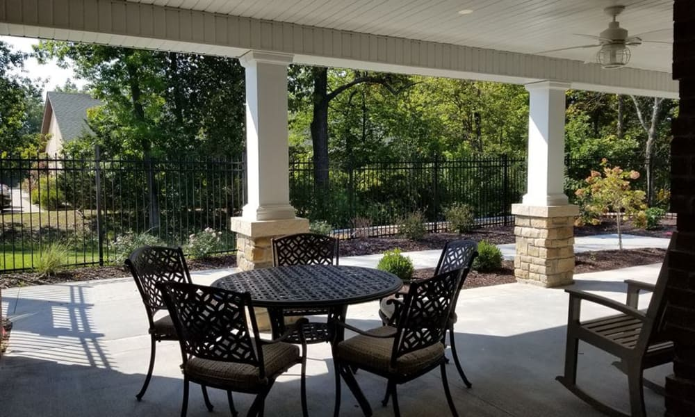 Outdoor patio with seating and tables at The Arbors at Harmony Gardens in Warrensburg, Missouri