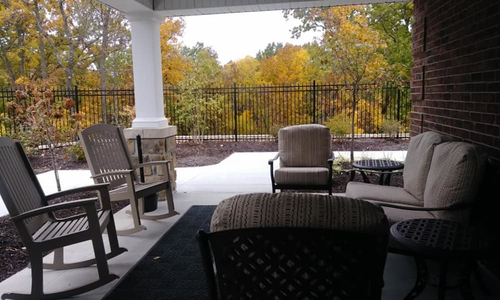 Rocking chairs on an outdoor patio at The Arbors at Harmony Gardens in Warrensburg, Missouri