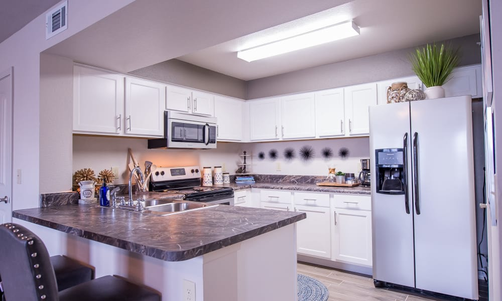 Kitchen with a breakfast bar at Scissortail Crossing Apartments in Broken Arrow, Oklahoma