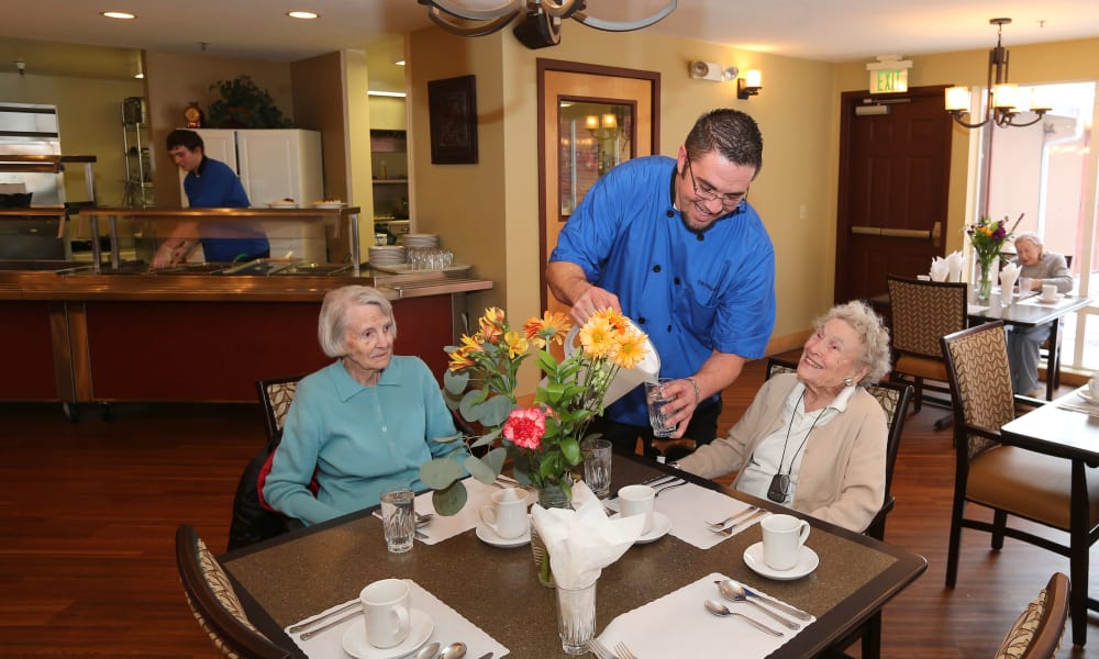 2 Senior women being served food at Elk Meadows Assisted Living in Oakley, Utah