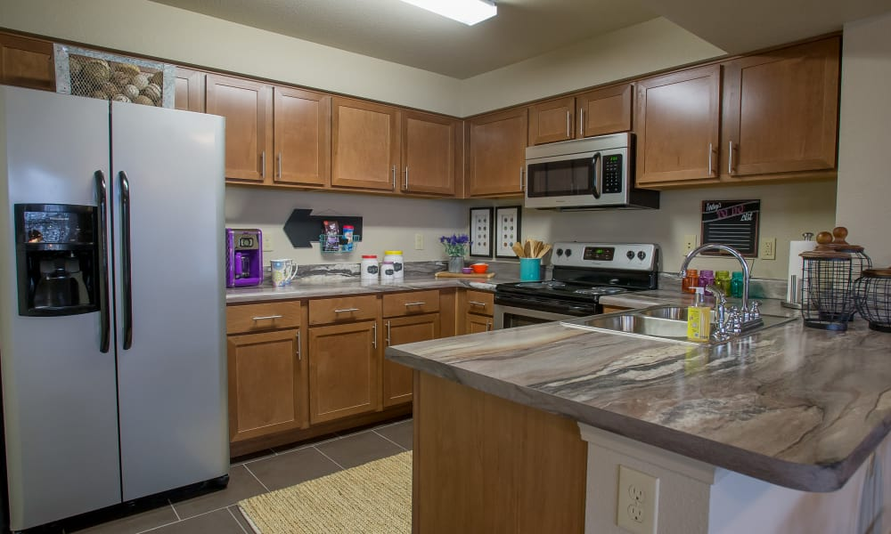 Kitchen with granite counters and stainless steel appliances at Portofino Apartments in Wichita, Kansas