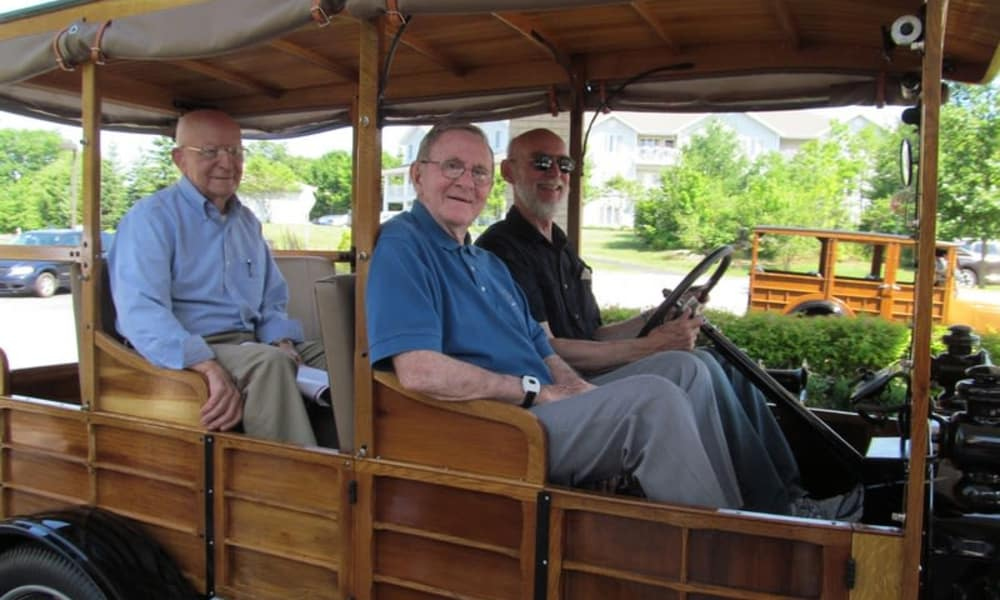 Three residents in a wooden car at Heritage Meadows Gracious Retirement Living in Cambridge, Ontario