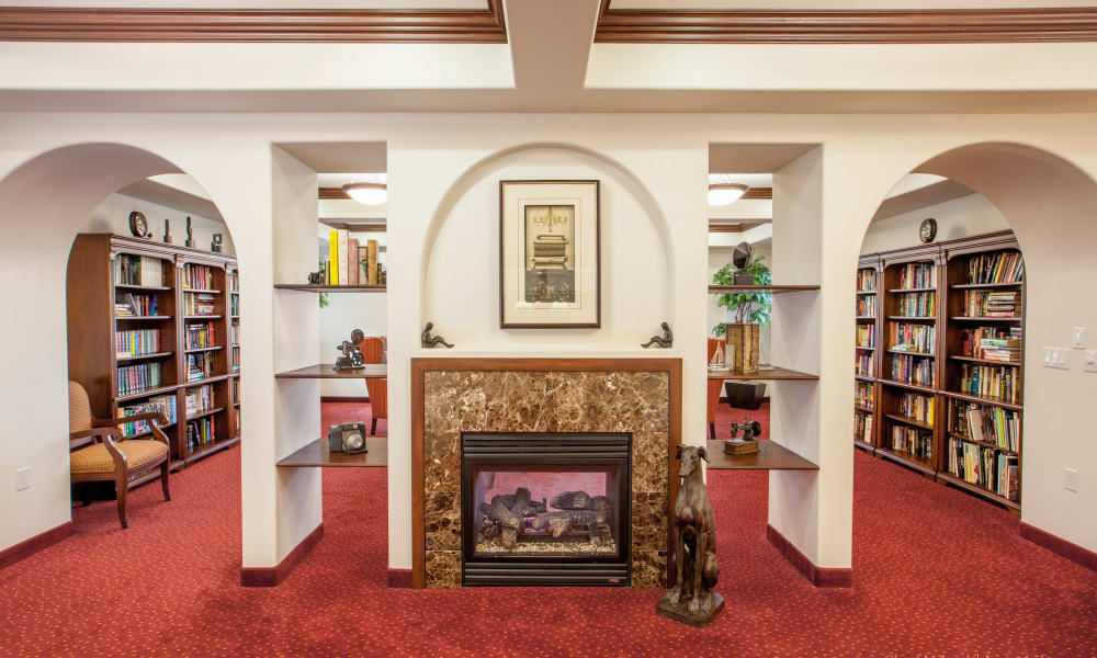 Community library with a fireplace at Heritage Meadows Gracious Retirement Living in Cambridge, Ontario