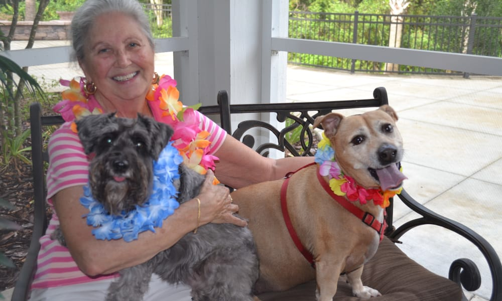 A resident on the porch with her two dogs at Julian Estates Gracious Retirement Living in Puyallup, Washington