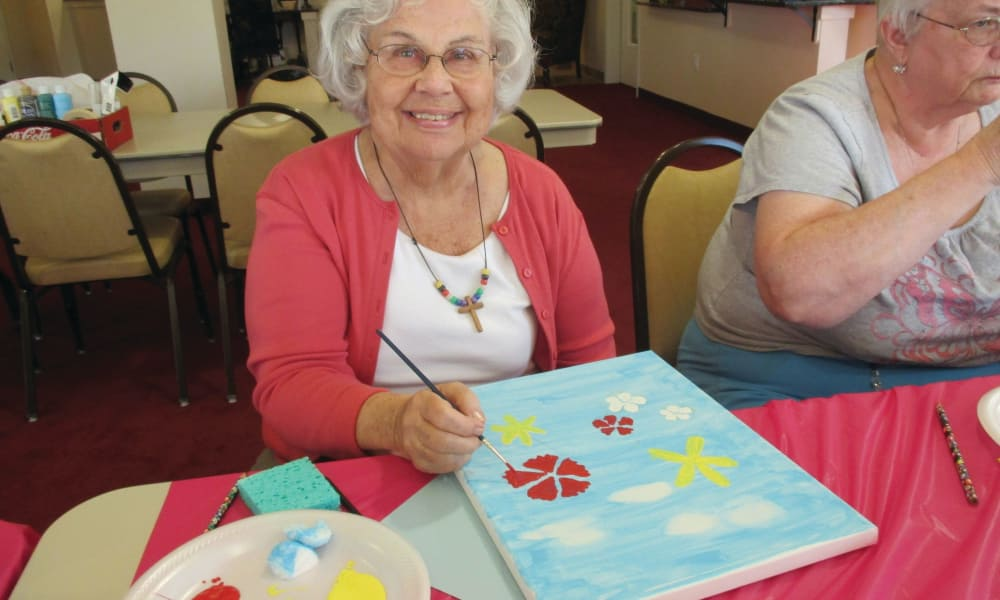 A happy resident painting at Julian Estates Gracious Retirement Living in Puyallup, Washington
