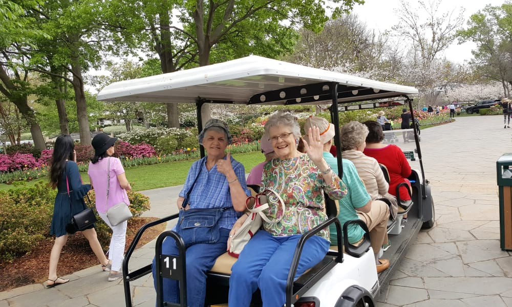 A group of residents on a large golf cart at Liberty Heights Gracious Retirement Living in Rockwall, Texas