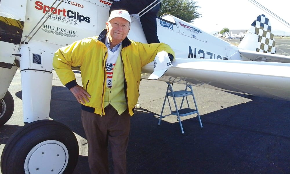 A resident from Liberty Heights Gracious Retirement Living in Rockwall, Texas posing for a photo next to a plane