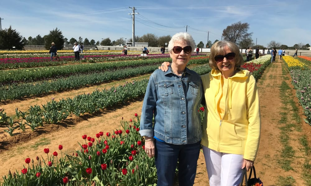 Two residents from Liberty Heights Gracious Retirement Living in Rockwall, Texas posing for a photo in a flower field