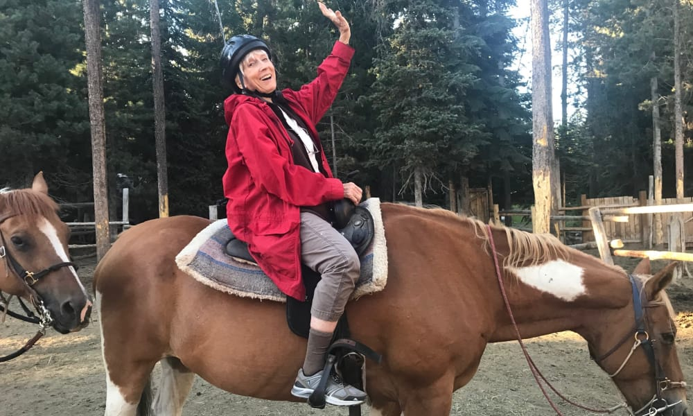 A happy resident from Linwood Estates Gracious Retirement Living in Lawrenceville, Georgia riding a horse