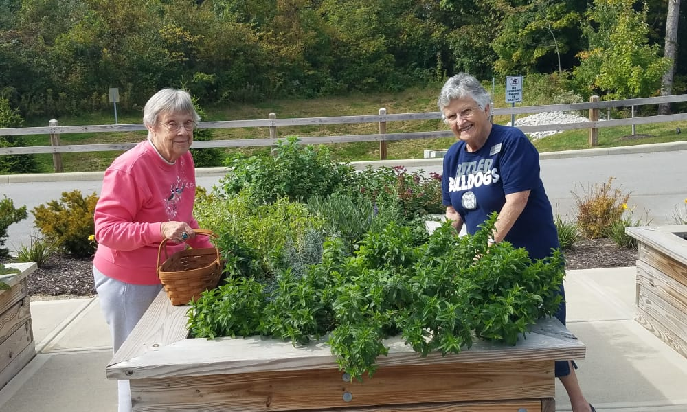 Two residents caring for plants in a planter box at Magnolia Heights Gracious Retirement Living in Franklin, Massachusetts