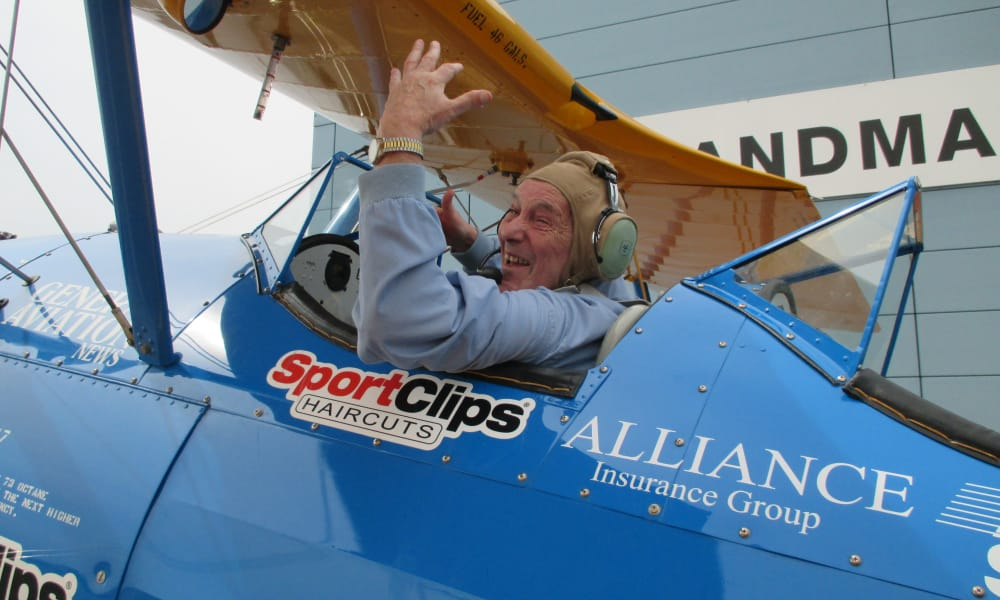 An excited resident from Maple Ridge Gracious Retirement Living in Cedar Park, Texas in a plane