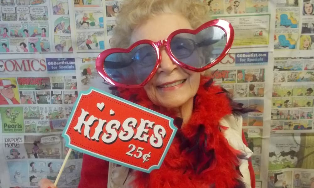 A resident posing with a kisses twenty five cents sign at Maple Ridge Gracious Retirement Living in Cedar Park, Texas
