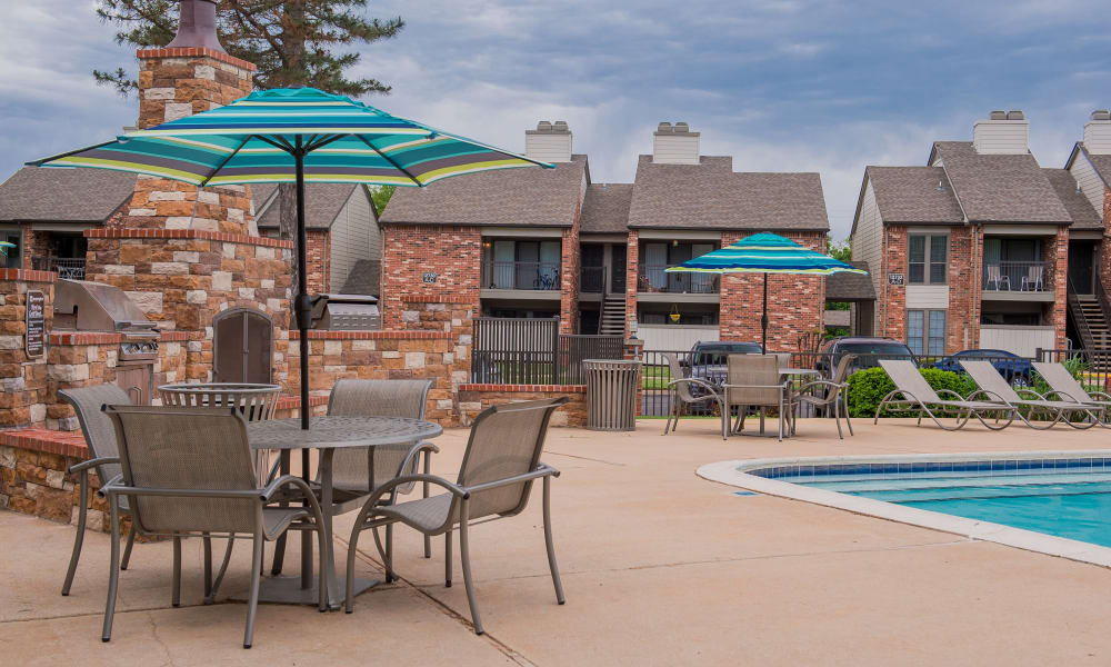 A table with an umbrella by the pool at The Warrington Apartments in Oklahoma City, OK