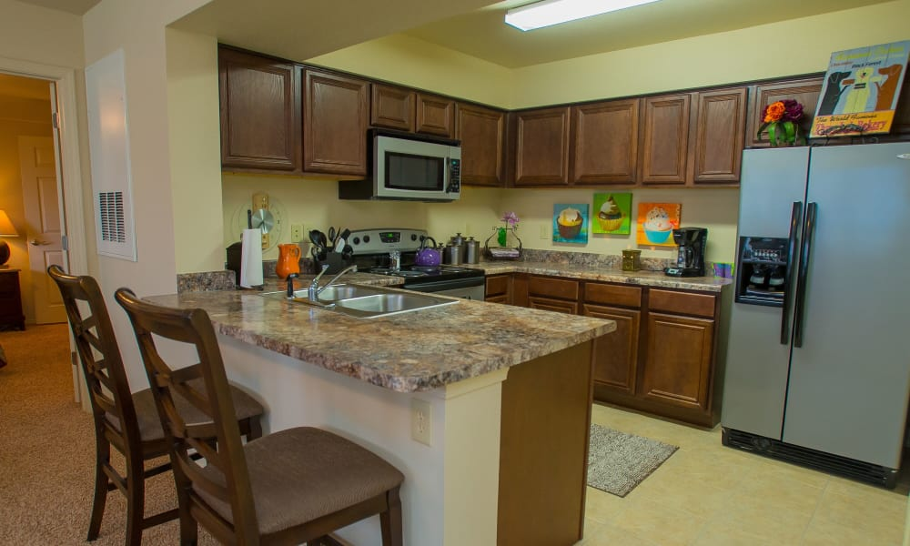 Kitchen with bar seating at Coffee Creek Apartments in Owasso, Oklahoma