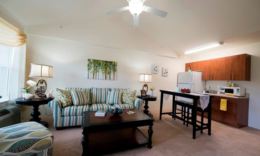 A well decorated living room and open kitchen at Northridge Gracious Retirement Living in Fishers, Indiana