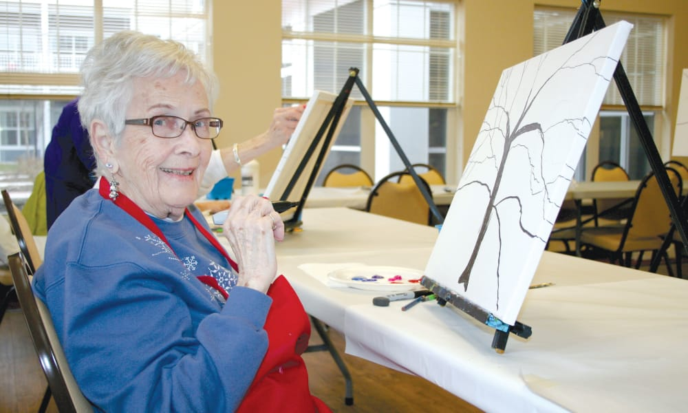 A happy resident painting a tree at Northridge Gracious Retirement Living in Fishers, Indiana
