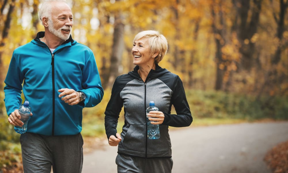 Senior couple jogging in a forest and having fun near The Oaks at Four Corners in Silver Spring, Maryland