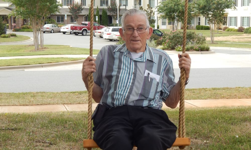 A resident on a swing in front of Oak Park Retirement in Salisbury, North Carolina