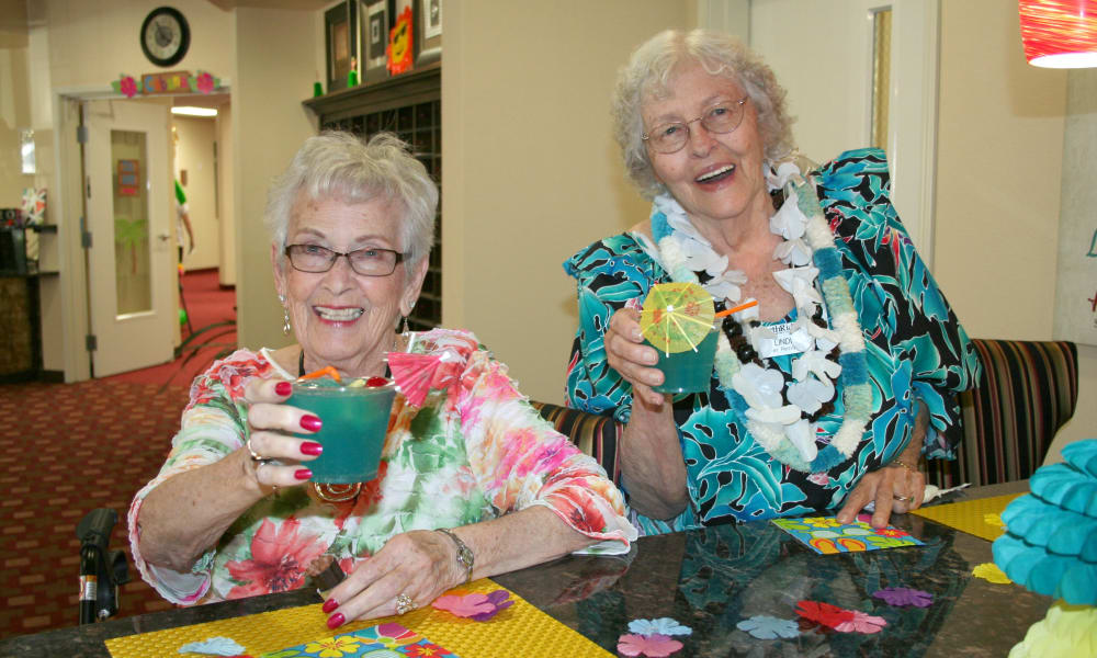 Two residents having drinks at a tropical themed party at Paloma Landing Retirement Community in Albuquerque, New Mexico